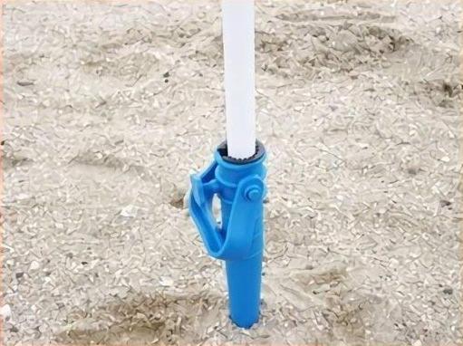砂地に突き刺さるビーチパラソルスタンド